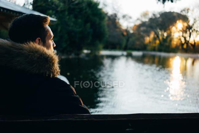 Vista traseira do homem de casaco quente sentado e olhando para o lago no pôr do sol. — Fotografia de Stock