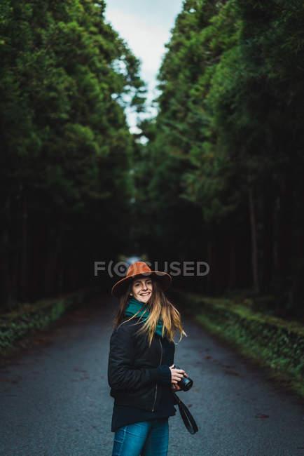 Fröhliche junge Frau steht mit Kamera auf Asphaltstraße im Wald. — Stockfoto