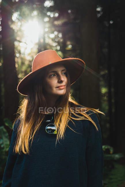 Joven mujer bonita en sombrero de pie en el bosque soleado y mirando hacia otro lado . - foto de stock