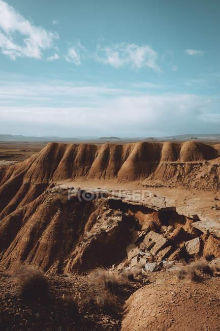 Vista para colinas secas arenosas com borda de rachaduras em dia nublado . — Fotografia de Stock