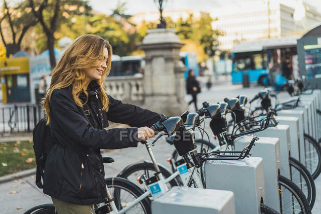 Femme gaie prenant vélo dans le parc — Photo de stock