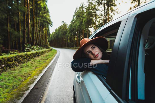 Giovane donna in cappello appoggiato fuori dal finestrino macchina su strada forestale — Foto stock