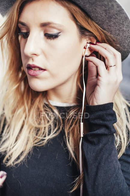 Young blonde woman listening music with earphones — Stock Photo