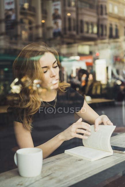 Blick durch die Fenster der jungen Frau Lesebuch im café — Stockfoto