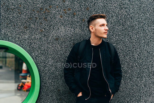 An in black jacket leaning on gray wall and looking pensively away. — Stock Photo