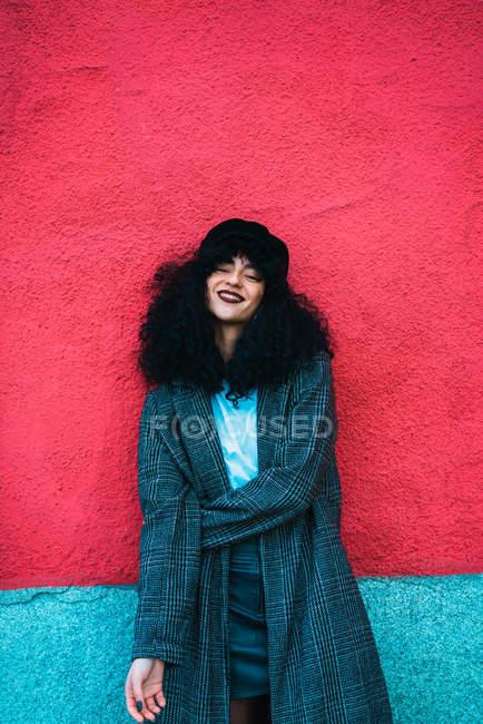Élégante femme frisée appuyé au mur coloré et regardant la caméra — Photo de stock