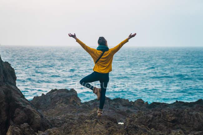 Rückansicht der Frau am Meer auf einem Bein mit Handzeichen auseinander — Stockfoto