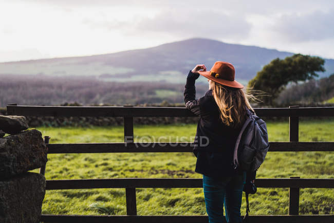 Rear view of woman leaning at rural fence on field — Stock Photo