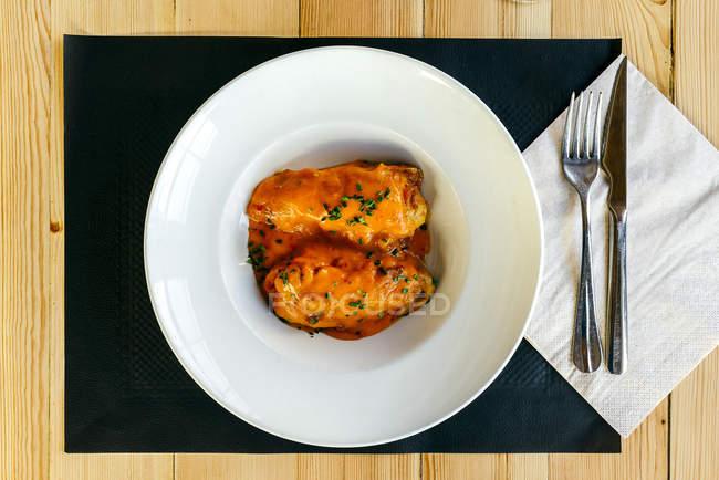 Peperoni ripieni con salsa sul piatto — Foto stock