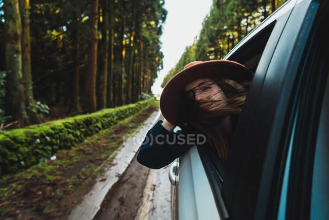 Donna in cappello che appende fuori auto sulla strada forestale — Foto stock