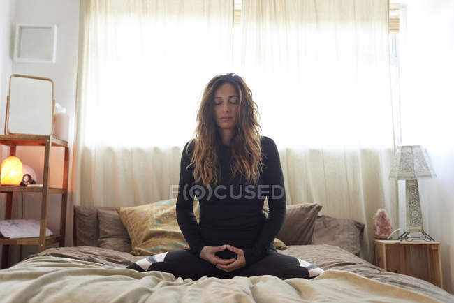 Brunette woman doing yoga exercises at home — Stock Photo