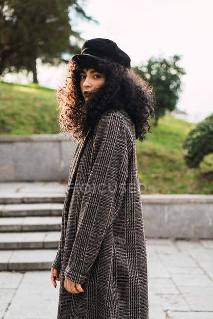 Side view of pretty curly woman in stylish coat posing in city park. — Stock Photo