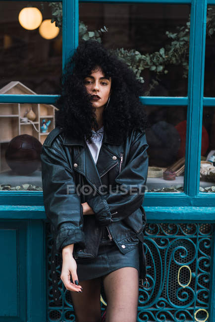 Pretty curly brunette woman standing at case on city street. — Stock Photo