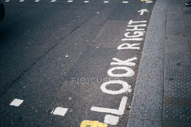 Handwritten inscription Look right painted with white color on gray sidewalk — Stock Photo