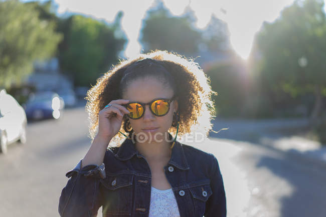 Stylish girl in sunglasses posing at street — Stock Photo