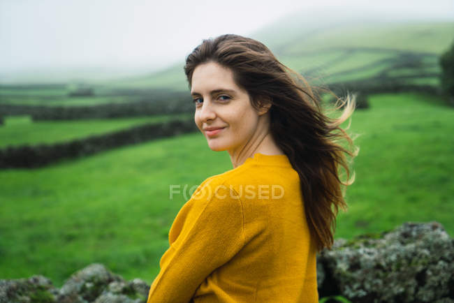 Cheerful young woman standing at green field and looking over shoulder at camera. — Stock Photo