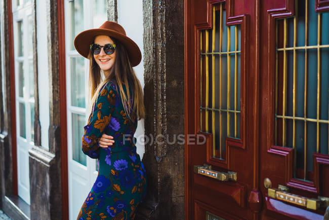 Mulher elegante alegre no chapéu inclinando-se na entrada na rua — Fotografia de Stock