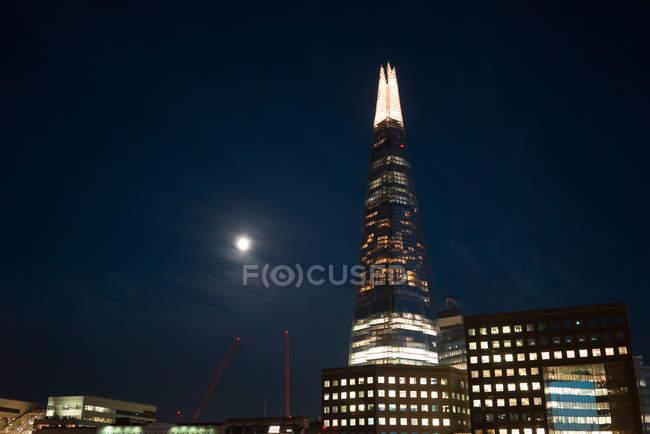 Светящийся небоскреб в современном районе против ночное небо с Луны. — стоковое фото