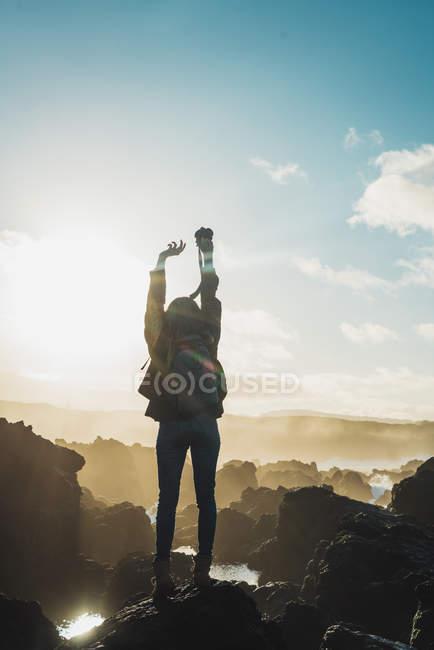 Rückansicht der Frau mit Kamera auf Klippe über sonnige Himmel — Stockfoto