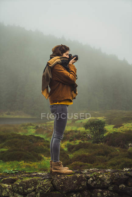 Woman taking photo on background of misty woods — Stock Photo