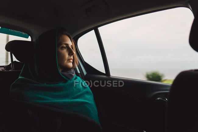 Женщина в шарф, езда на заднем сиденье в автомобиле и мечтательно глядя в окно — стоковое фото