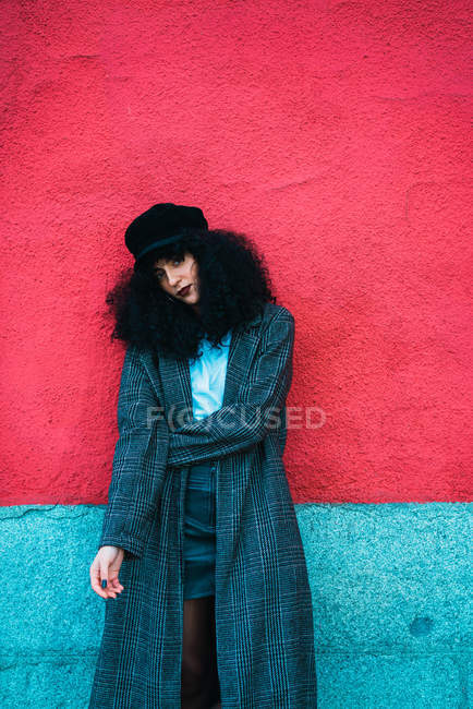 Young brunette curly woman standing in stylish coat and posing at bright wall. — Stock Photo