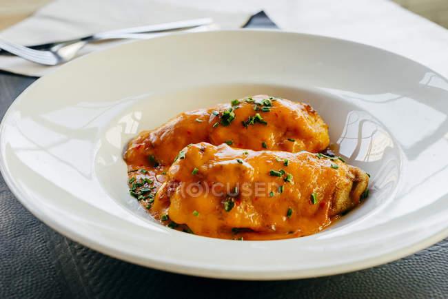 Peperoni ripieni con salsa sul piatto bianco — Foto stock