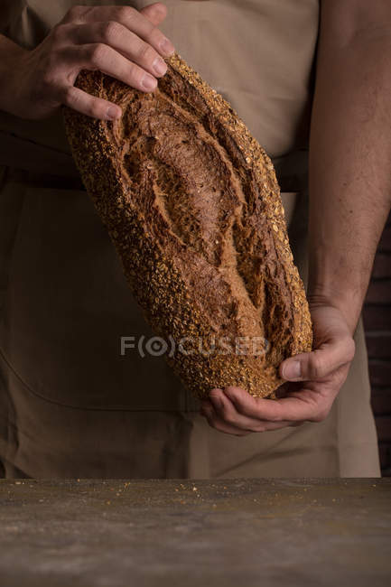 Crop male hands  holding freshly baked bread — Stock Photo