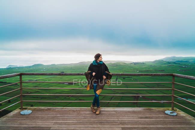 Молодая женщина стоит на террасе с расширенным видом на зеленые земли под облаками . — стоковое фото