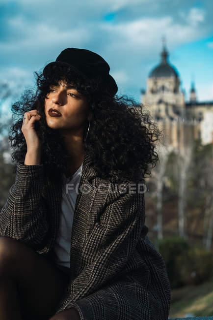 Jeune femme élégante assise sur le fond de façade ornée au crépuscule — Photo de stock