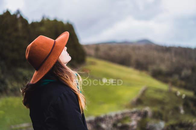 Seitenansicht junge Frau mit Hut posiert auf dem Land — Stockfoto