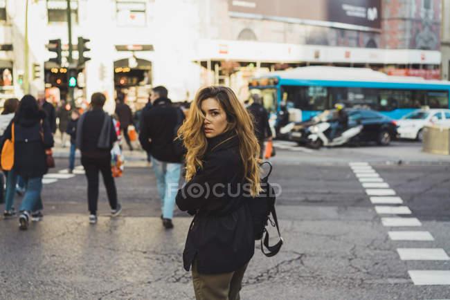 Jolie femme avec sac à dos regardant en arrière sur la route de la ville . — Photo de stock