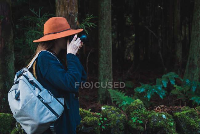 Vista laterale della donna turistica con zaino prendendo colpi in foresta verde — Foto stock