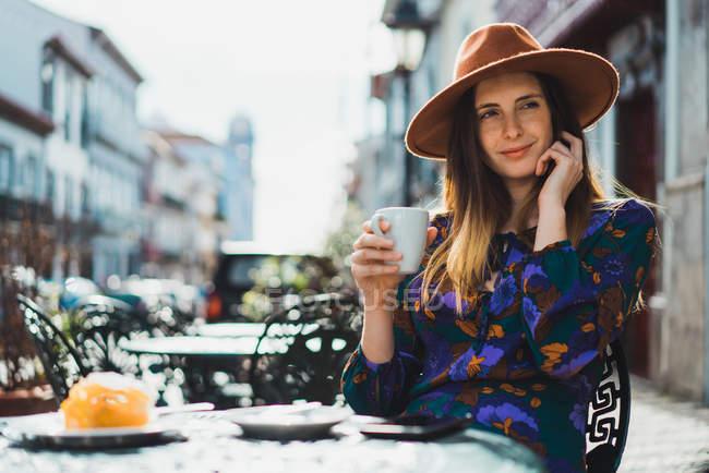 Жінка п'є каву столом зовні кафе — стокове фото