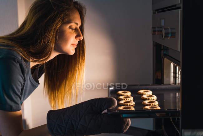 Vue de côté de jeune fille, vérification des progrès de faire des cookies sur la plaque de tôle au four. — Photo de stock