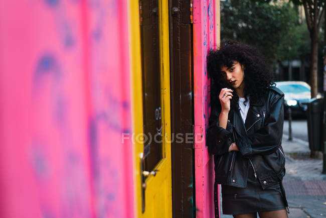 Glamour curly woman in leather clothes leaning on pink wall and looking at camera — Stock Photo