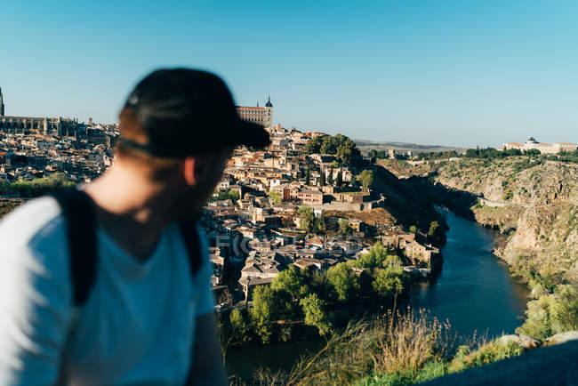 Туристична людина дивиться через плече назад на місто в горах — стокове фото