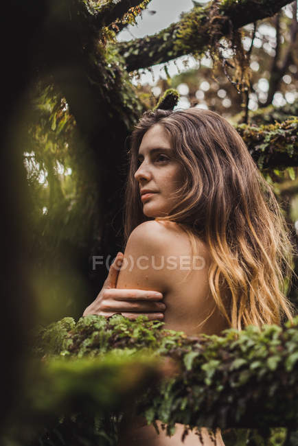 Naked woman embracing shoulder among mossy tree branches and looking away. — Stock Photo
