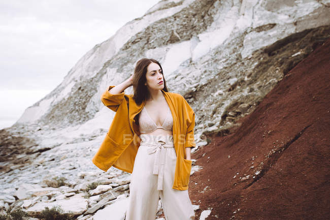 Brunette girl in bra and jacket posing over rocky cliff — Stock Photo