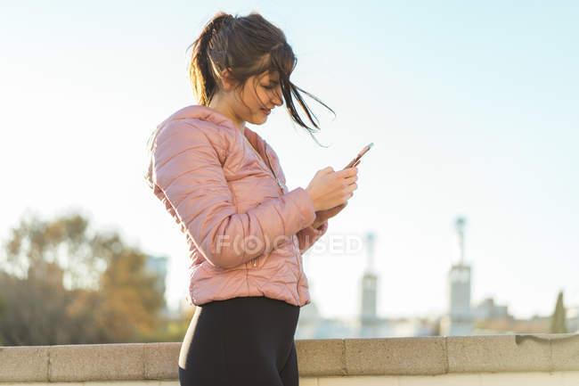 Vue latérale de la jeune femme debout sur la rue et utilisant un smartphone . — Photo de stock
