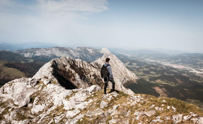 Back view of tourist man with backpack standing on mountain and looking away. — Stock Photo