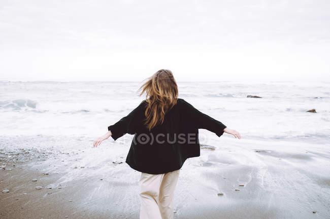 Вид сзади на женщину на берегу океана — стоковое фото