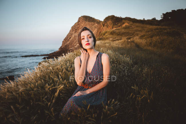 Young confident brunette in summer dress sitting in dry grass of terrain on coastline. — Stock Photo