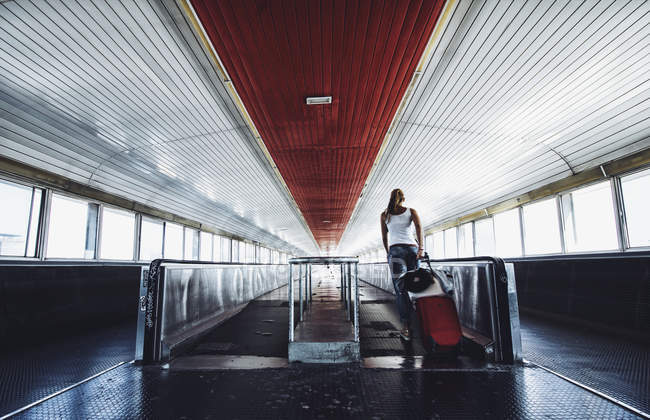 Back view of woman with suitcase stepping on travelator on the station. — Stock Photo