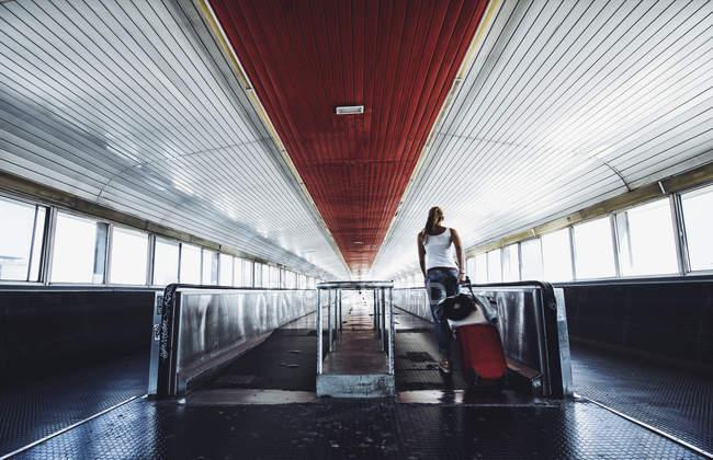 Vue arrière de la femme avec valise marchant sur le voyageur sur la station . — Photo de stock