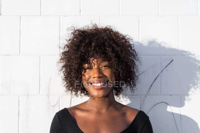 Portrait of cheerful woman posing at white wall — Stock Photo