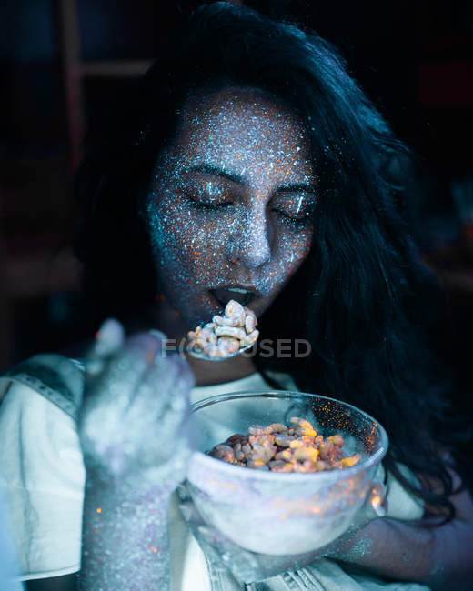 Woman with glitters on face eating cereal — Stock Photo