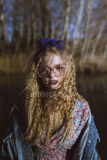 Jeune fille blonde frisée dans des verres posant dans la nature — Photo de stock