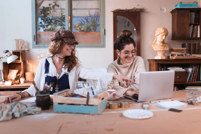 Cheerful pretty women sitting together and using laptop in workshop. — Stock Photo