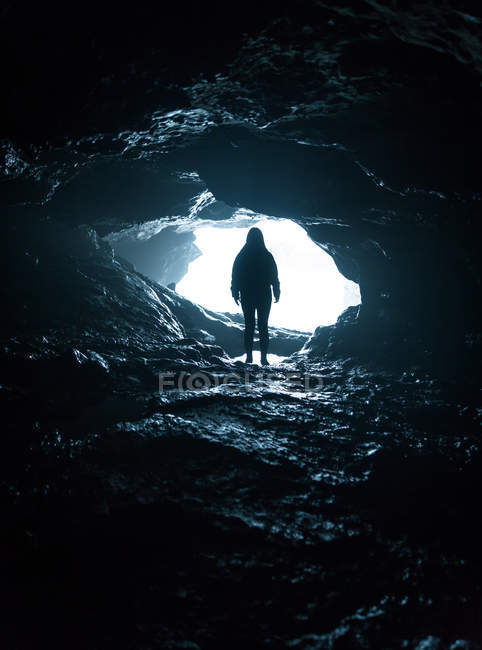 Silhouette of unrecognizable person standing at cave entrance. — Stock Photo